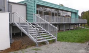 breite Treppe außen mit Geländer um das Gebäude